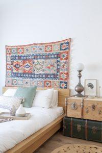 Dormitorio con baúles, lámpara y tapiz